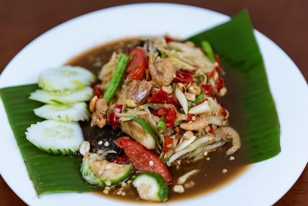 Thai green papaya salad, som tum thai spicy, closeup