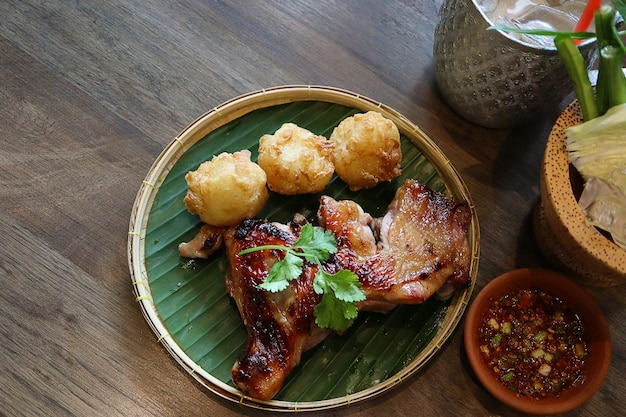 Thai grilled chicken with fried sticky rice mix egg on threshing basket and spicy thai sauce style.