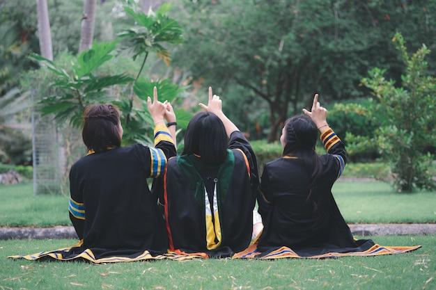 졸업식 드레스를 입은 태국 여성들이 공원에 뒤에서 앉아 있다.