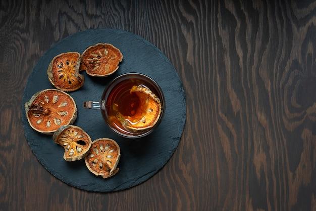 Тайский лечебный чай матум из кусочков сушеных фруктов баэль в стеклянной чашке на деревянном