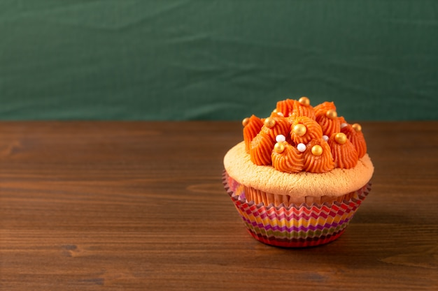 Thai ice tea cupcake on wooden board and green background with copy space