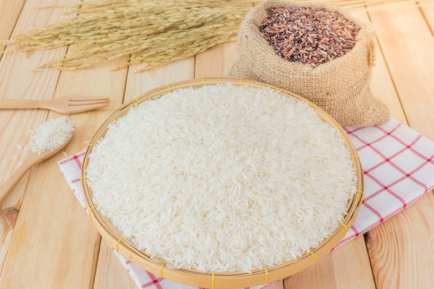 Thai jasmine white rice and riceberry rice in bamboo basket and bag on wooden background