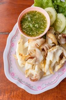 매운 소스와 함께 접시에 태국 현지 음식 구운 오징어