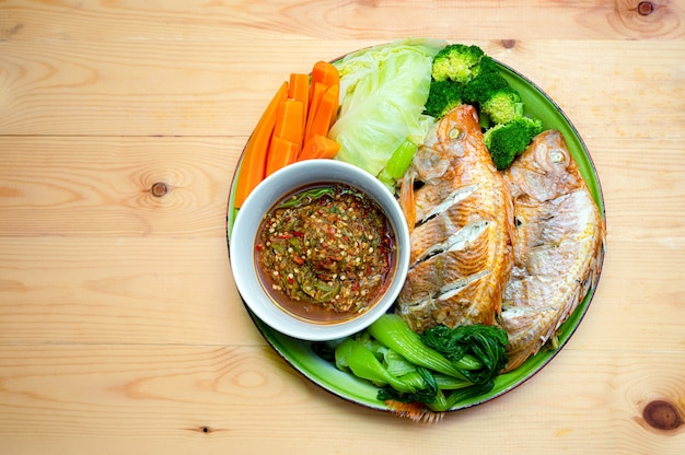Thai local food style steamed red tilapia fish with vegetable herb on dish, thai traditional culture food