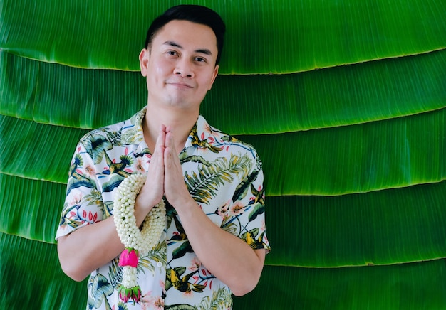 Thai man doing pay respect posture with jasmine garland on his arm to do blessing for songkran festival concept.