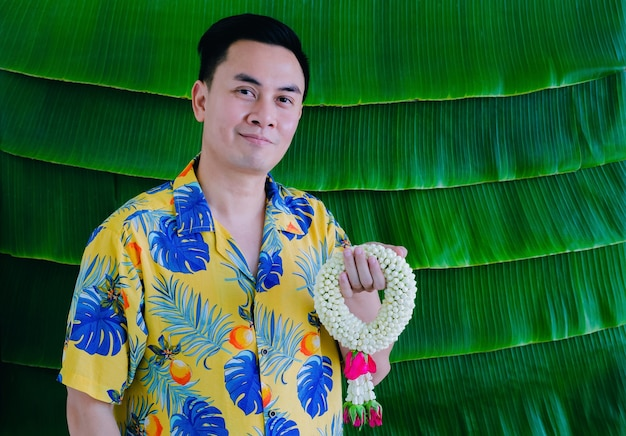 Thai man holding jasmine garland to give blessing for songkran festival with banana leaf background.