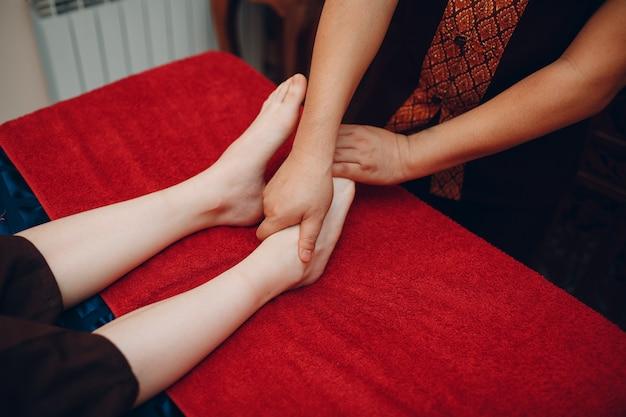 Тайский мужчина делает процедуру классического тайского массажа ног молодой женщине в спа-салоне красоты