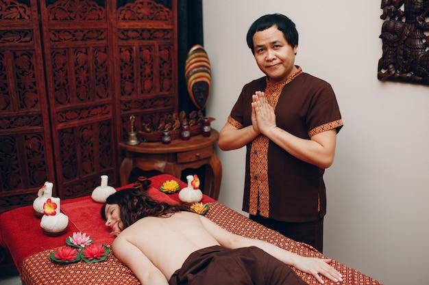 Тайский мужчина делает процедуру классического тайского массажа молодой женщине в спа-салоне красоты