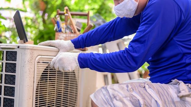Тайский мужчина онлайн учится и ремонтирует кондиционер в домашних условиях. новая нормальная жизнь после covid-19. блокировка и самокарантин. оставайся дома и держись на расстоянии.