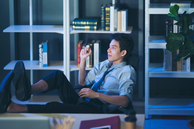 Thai man relaxed confident young businessman sleep with legs on desk at office work
