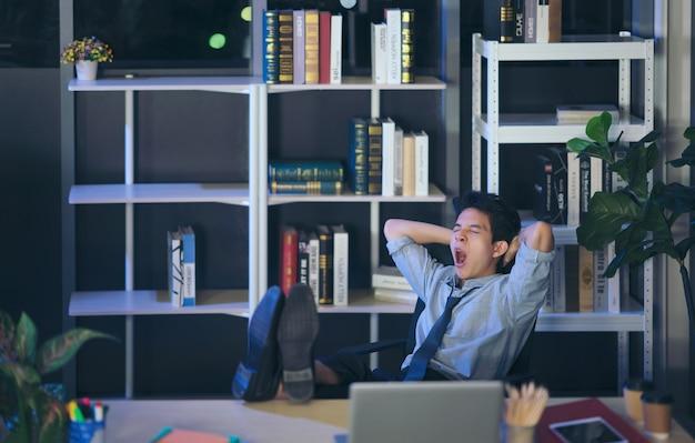 タイの男性は、事務作業で机の上の足でリラックスした自信を持って青年実業家睡眠