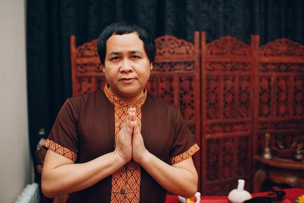 전통적인 태국 양복과 환영기도 제스처 접힌 손으로 태국 사람 웃는 초상화.
