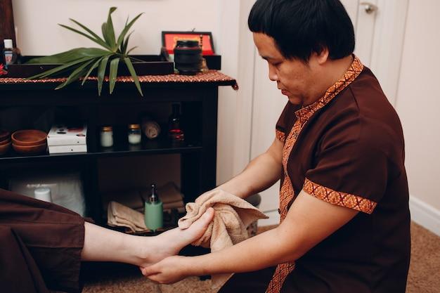 Тайский мужчина моет ноги и делает процедуру классического тайского массажа молодой женщине в спа-салоне красоты