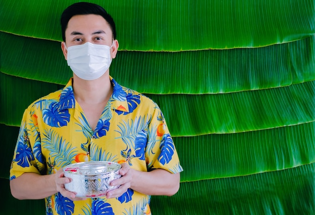 Thai man wearing face mask holding water bowl that have flowers to give blessing for new normal songkran festival concept.