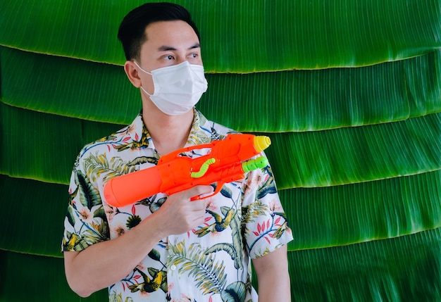 Thai man wearing face mask with water gun for new normal songkarn festival concept on banana leaf background.