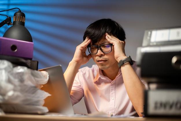 Тайский менеджер человек, использующий руку для расслабления головы после того, как не может придумать, как решить решение для выполнения проекта в офисе. головная боль и депрессия. перегрузка после работы из дома.