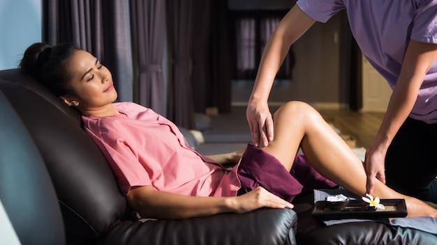 소파에 앉아 아름다운 아시아 여성을 위한 태국 마사지 종아리와 다리 치료