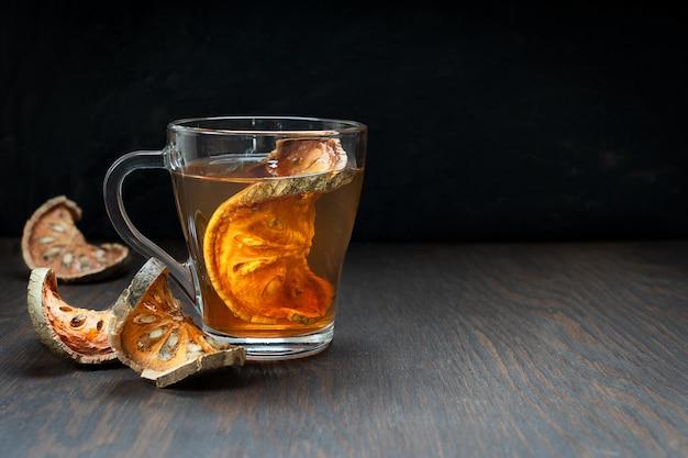 Тайский чай матум из кусочков сушеных фруктов баэль в стеклянной чашке на темно-коричневом деревянном столе
