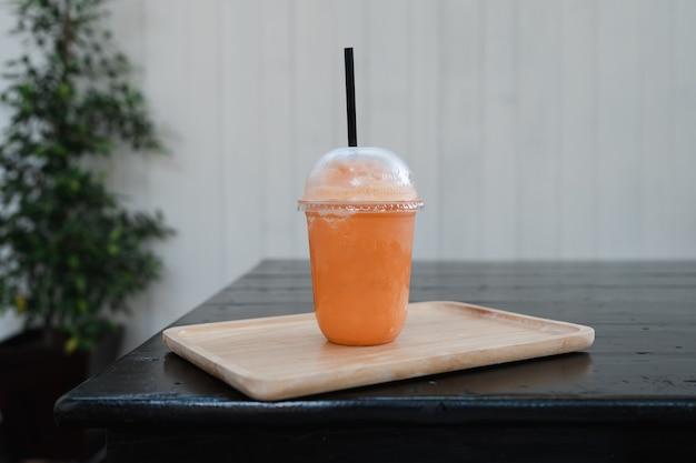 テイクアウトカップのタイのミルクティーフラッペは、黒い木製のテーブルの上に木製のトレイを添えて