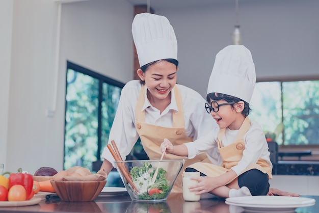 Thai mom and kid cooking together at home. social distancing and stay home stay safe. family activity effect from covid-19 and stop outbreak virus. lock down and self-quarantine at home.