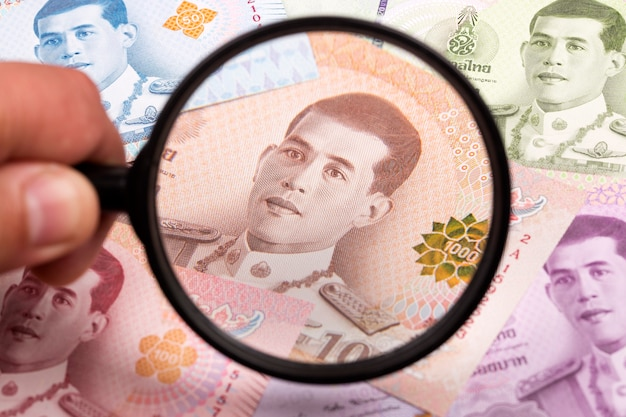 Тайские деньги в увеличительном стекле бизнес-фон