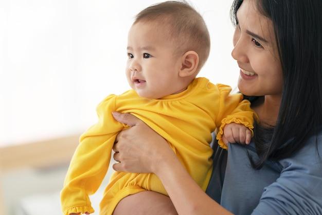 タイのお母さんは赤ちゃんを慰めています。彼女の腕の中で生まれたばかりの赤ちゃんを保持している女性