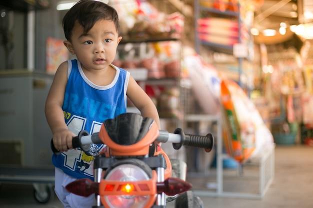 Thai naughty boy riding his motorcycle, smart boy playing with motor bike.
