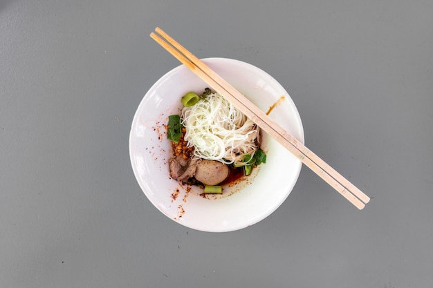 Thai noodle dry vermicelli with porks in tiny white bowl on grey rustic table.