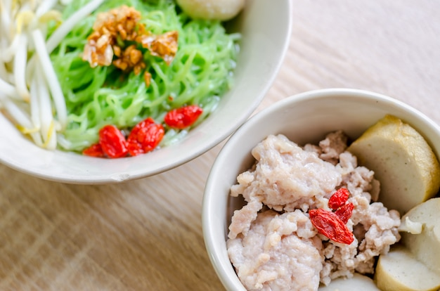 Тайская лапша с рыбным шаром и хрустящей свиной кожей на деревянном фоне. тайская еда