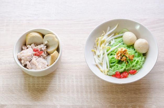 Тайская лапша с мясным мясом и хрустящей свиной кожей на деревянном фоне. тайская еда