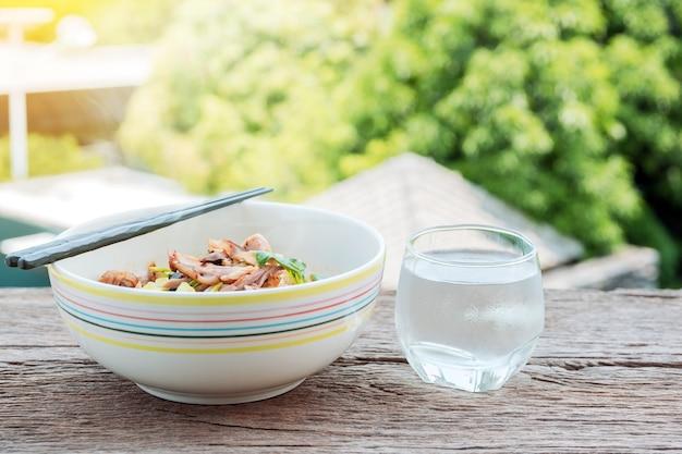タイの麺と美しい自然の背景を持つ古い木製のテーブルに水を飲みます。