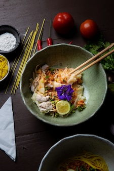 Thai noodles and flavoring ingredients placed on a wooden table