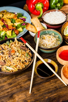 Thai noodles; salad; spring rolls; rice; beans sprouts; sauces with chopsticks on wooden table