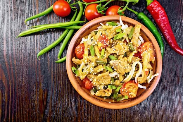 Тайская лапша вок с куриным мясом, помидорами, соевым соусом и стручковой фасолью, посыпанная кунжутом, в тарелке на фоне деревянной доски сверху