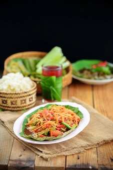 Thai northeast food called som tam or spicy green papaya salad with side dishes