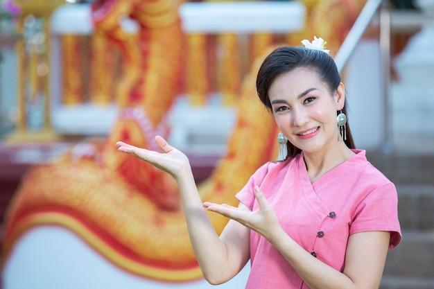 Signora del nord thailandese sorridente in camicia rosa