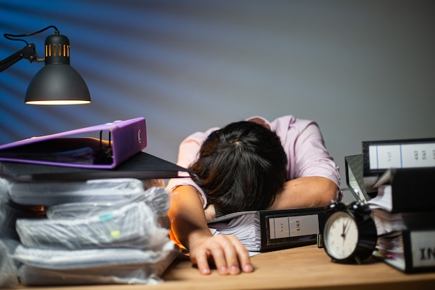 Тайский офисный человек, сонный персонал, спит на столе после завершения отчета в ночное время. бизнесмен на рабочем месте для выполнения крайнего срока проекта. азиатский взрослый лежит для отдыха со своим отчетом.