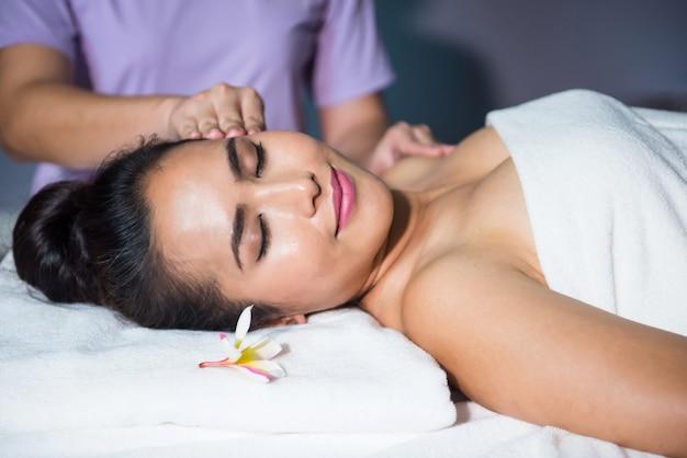 아시아 아름다운 젊은 여성 노화 방지 얼굴 치료에 침대에 타이어 오일 얼굴 마사지