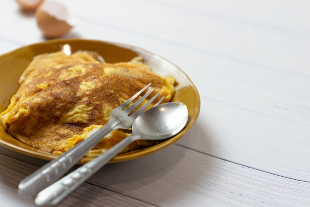 Thai omelette or fried egg little scorched on brown ceramic dish with spoon.