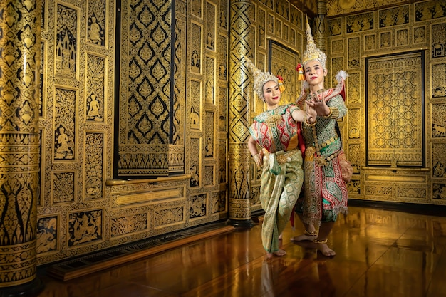 Thai pantomime actresses sita and rama are flirting with each other. in the area of a beautiful golden thai style house