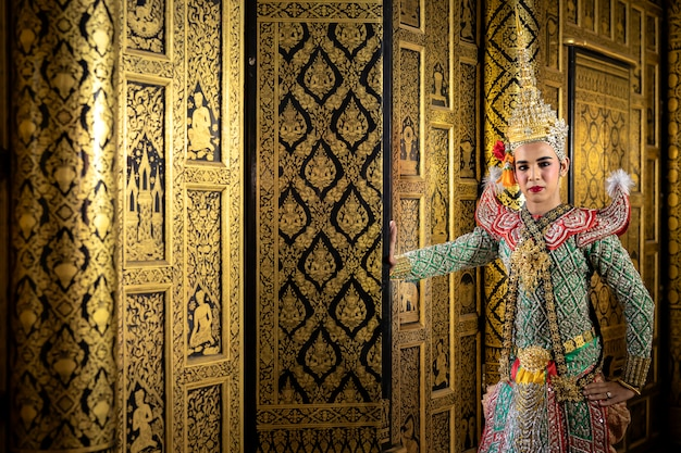 Thai pantomime character in the role of rama standing at the house of ancient thai style, golden beauty