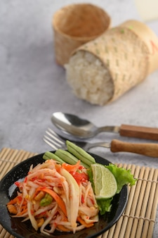Thai papaya salad in a black plate with sticky rice