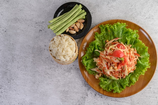 Thai papaya salad on salad in a wooden plate with sticky rice, yardlong beans, and garlic