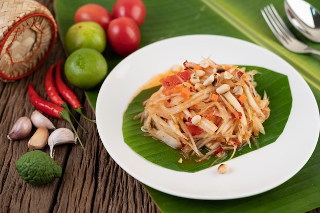 Thai papaya salad in a white plate on banana leaves with lime, tomatoes, eggplant, chili, garlic, peppers, salad, and peanuts.