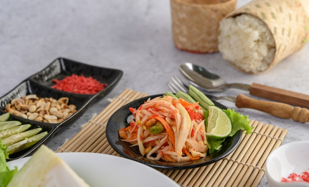 Thai papaya salad in a white plate with sticky rice and dried shrimps