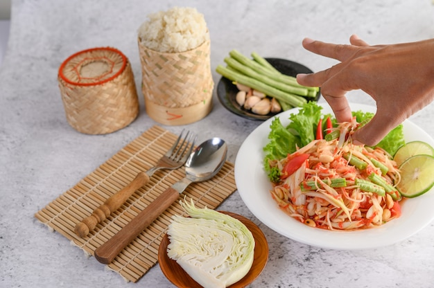 Thai papaya salad in a white plate with sticky rice