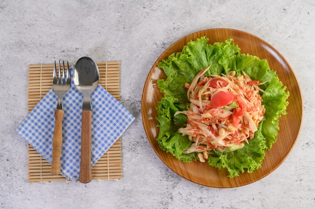 Thai papaya salad in a wooden plate with cutlery