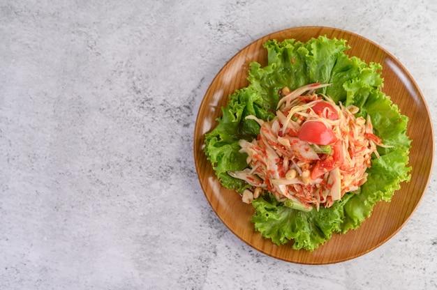 Thai papaya salad on a wooden plate