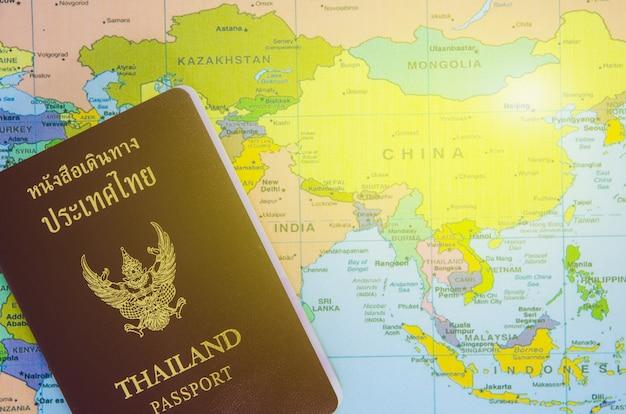 タイのパスポートがアジアの地図の上に横たわる