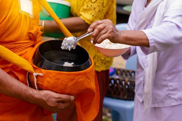 タイの人々は仏教徒の貸し日の終わりに僧侶の施しのボウルに食べ物を入れる